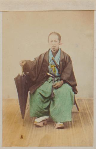 Shimooka Renjō, 'Tsūji (Interpreter)'/ 'Japanese Interpreter', c.1863-70. A samurai official or yakunin poses with an imported umbrella.